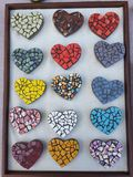 Ζωηρόχρωμοι διαμορφωμένοι καρδιά μαγνήτες μωσαϊκών μέσα σε ένα ξύλινο πλαίσιο εικόνων στοκ φωτογραφία