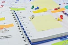 Ζωηρόχρωμοι κολλώδεις σημειώσεις, συνδετήρας και καρφίτσα στη σελίδα ημερολογίων Στοκ Εικόνα
