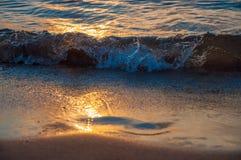 Ζωηρόχρωμοι κυματισμοί ως σύνολα ήλιων πέρα από το νερό στοκ φωτογραφία με δικαίωμα ελεύθερης χρήσης