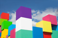Ζωηρόχρωμοι κύβοι ενάντια στα άσπρα σύννεφα μπλε ουρανού Κίτρινοι, κόκκινοι, πράσινοι, ρόδινοι χρωματισμένοι φραγμοί Έννοια χρωμά Στοκ Εικόνα