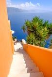 Ζωηρόχρωμοι πορτοκαλιοί τοίχοι και άσπρη σκάλα με το ωκεάνιο υπόβαθρο Στοκ φωτογραφίες με δικαίωμα ελεύθερης χρήσης