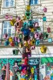 Ζωηρόχρωμοι τροφοδότες πουλιών που κλείνουν το τηλέφωνο στο δέντρο κοντά Στοκ εικόνες με δικαίωμα ελεύθερης χρήσης