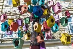 Ζωηρόχρωμοι τροφοδότες πουλιών που κλείνουν το τηλέφωνο στο δέντρο κοντά Στοκ Φωτογραφία