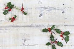 Ζωηρόχρωμος παραδοσιακός ελαιόπρινος Χριστουγέννων με τα κόκκινα μούρα στην ξύλινη σύσταση grunge των παλαιών ξεπερασμένων πινάκω Στοκ εικόνες με δικαίωμα ελεύθερης χρήσης