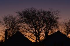 Ζωηρόχρωμος πορφυρός πορτοκαλής ουρανός ανατολής με τα σπίτια σκιαγραφιών στα ήρεμα προάστια στοκ φωτογραφίες με δικαίωμα ελεύθερης χρήσης