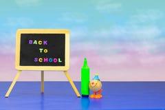 Ζωηρόχρωμος σχολικός εξοπλισμός και ένας αστείος κλόουν παιχνιδιών στη σκούρο μπλε ετικέττα στοκ εικόνες
