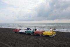 Ζωηρόχρωμος της βάρκας πενταλιών που σταθμεύουν στην παραλία, συννεφιασμένος, σύννεφα, κύματα στοκ εικόνα