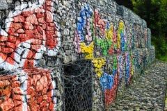 Ζωηρόχρωμος τοίχος των τούβλων με τα γκράφιτι στις πέτρες Στοκ φωτογραφία με δικαίωμα ελεύθερης χρήσης