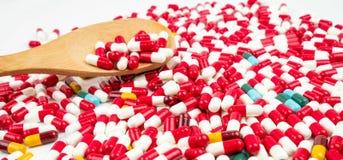 Ζωηρόχρωμος των αντιβιοτικών χαπιών καψών και του ξύλινου κουταλιού στο λευκό Στοκ Εικόνες