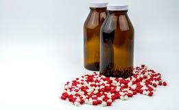 Ζωηρόχρωμος των αντιβιοτικών χαπιών καψών με δύο ηλέκτρινα μπουκάλια γυαλιού στο άσπρο υπόβαθρο Στοκ Εικόνες