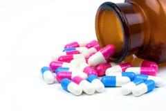 Ζωηρόχρωμος των αντιβιοτικών χαπιών καψών με το ηλέκτρινο μπουκάλι γυαλιού που απομονώνεται στο άσπρο υπόβαθρο Στοκ Φωτογραφία