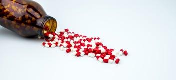 Ζωηρόχρωμος των αντιβιοτικών χαπιών καψών με το ηλέκτρινο μπουκάλι γυαλιού στο άσπρο υπόβαθρο Στοκ Εικόνες