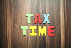 Ζωηρόχρωμος φορολογικός χρόνος λέξης στο ξύλινο υπόβαθρο Στοκ Φωτογραφία