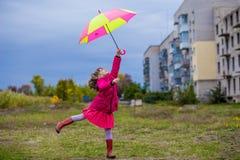 Ζωηρόχρωμο άλμα κοριτσιών ομπρελών χαριτωμένο αστείο στον ουρανό Στοκ Εικόνα
