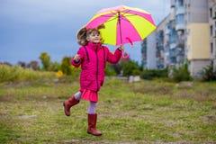 Ζωηρόχρωμο άλμα κοριτσιών ομπρελών χαριτωμένο αστείο στον ουρανό Στοκ εικόνα με δικαίωμα ελεύθερης χρήσης