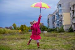 Ζωηρόχρωμο άλμα κοριτσιών ομπρελών χαριτωμένο αστείο στον ουρανό Στοκ εικόνες με δικαίωμα ελεύθερης χρήσης
