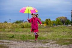 Ζωηρόχρωμο άλμα κοριτσιών ομπρελών χαριτωμένο αστείο στον ουρανό Στοκ Εικόνες