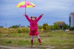 Ζωηρόχρωμο άλμα κοριτσιών ομπρελών χαριτωμένο αστείο στον ουρανό Στοκ Φωτογραφίες