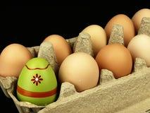 Ζωηρόχρωμο αυγό Πάσχας στην επιχείρηση των συνηθισμένων αυγών Στοκ Φωτογραφία