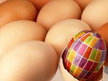 Ζωηρόχρωμο αυγό Πάσχας στην επιχείρηση των συνηθισμένων αυγών Στοκ Εικόνες