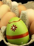 Ζωηρόχρωμο αυγό Πάσχας στην επιχείρηση των συνηθισμένων αυγών Στοκ Εικόνα
