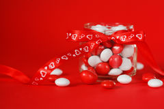 Ζωηρόχρωμο βάζο καραμελών που διακοσμείται με ένα κόκκινο τόξο με τις καρδιές στο κόκκινο υπόβαθρο ανασκόπησης η μπλε κιβωτίων κα Στοκ Φωτογραφίες