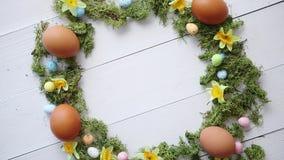Ζωηρόχρωμο διακοσμητικό στεφάνι αυγών Πάσχας στο άσπρο ξύλινο επιτραπέζιο υπόβαθρο απόθεμα βίντεο