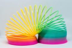 Ζωηρόχρωμο ελατήριο παιχνιδιών χρωματισμένο ύδωρ παιχνιδιών παιδιών χρώματα κινηματογράφηση σε πρώτο πλάνο πλαστικό Στοκ Φωτογραφία