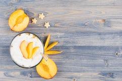 Ζωηρόχρωμο εύθυμο πρόγευμα με το γιαούρτι, ώριμο ροδάκινο φετών δημητριακών αστεριών στον μπλε ξύλινο πίνακα στοκ εικόνα με δικαίωμα ελεύθερης χρήσης