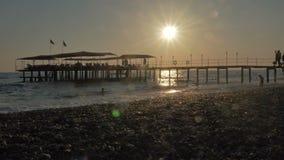 ζωηρόχρωμο ηλιοβασίλεμα Άποψη θάλασσας με τα κύματα και την παραλία αφρού, αποβαθρών και χαλικιών Σκιαγραφίες των ευτυχών επιπλεό φιλμ μικρού μήκους