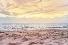 Ζωηρόχρωμο ηλιοβασίλεμα παραλιών με τον πορτοκαλή ουρανό, χαμηλή γωνία με τη μουτζουρωμένη άμμο στο πρώτο πλάνο Στοκ εικόνα με δικαίωμα ελεύθερης χρήσης