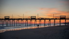 Ζωηρόχρωμο ηλιοβασίλεμα στην ωκεάνια ακτή με τη σκιαγραφία της αποβάθρας και της φωτογραφίας στοκ εικόνες