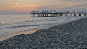 Ζωηρόχρωμο ηλιοβασίλεμα στη θάλασσα Όμορφη χαλικιώδης παραλία με τα κύματα και την αποβάθρα απόθεμα βίντεο