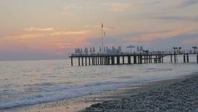 Ζωηρόχρωμο ηλιοβασίλεμα στη θάλασσα Όμορφη χαλικιώδης παραλία με τα κύματα και την αποβάθρα φιλμ μικρού μήκους