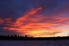 Ζωηρόχρωμο ηλιοβασίλεμα με τον τομέα στο πρώτο πλάνο Στοκ Φωτογραφία