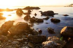 Ζωηρόχρωμο ηλιοβασίλεμα πέρα από τη Μεσόγειο με το χωριό στο υπόβαθρο στοκ φωτογραφίες