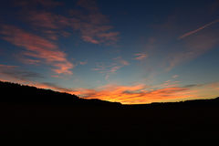 Ζωηρόχρωμο ηλιοβασίλεμα πέρα από τους λόφους Στοκ εικόνα με δικαίωμα ελεύθερης χρήσης