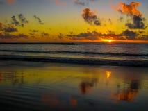 Ζωηρόχρωμο ηλιοβασίλεμα που απεικονίζει στη θάλασσα Στοκ Φωτογραφίες