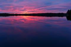 Ζωηρόχρωμο ηλιοβασίλεμα στη λίμνη με την αντανάκλαση Στοκ Φωτογραφία