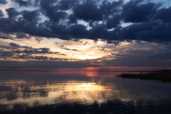 Ζωηρόχρωμο ηλιοβασίλεμα στη λίμνη Στοκ Εικόνες