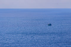 Ζωηρόχρωμο θαλάσσιο τοπίο με τη βάρκα ψαράδων ενάντια βαθιά σε μπλε Στοκ Φωτογραφία