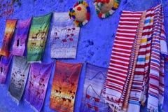 Ζωηρόχρωμο κλωστοϋφαντουργικό προϊόν στον μπλε τοίχο Στοκ εικόνες με δικαίωμα ελεύθερης χρήσης