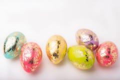 ζωηρόχρωμο λευκό αυγών Πάσχας ανασκόπησης 2 όλα τα αυγά Πάσχας έννοιας νεοσσών κάδων ανθίζουν τη χλόη χρωμάτισαν τις τοποθετημένε Στοκ φωτογραφία με δικαίωμα ελεύθερης χρήσης