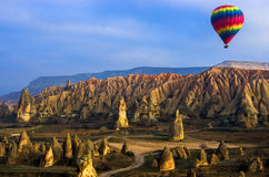 Ζωηρόχρωμο μπαλόνι ζεστού αέρα που πετά πέρα από το betwitching τοπίο Cappadocia, Τουρκία Στοκ φωτογραφίες με δικαίωμα ελεύθερης χρήσης