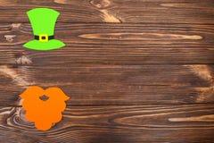 Ζωηρόχρωμο οριζόντιο έμβλημα θέματος ημέρας του ST Πάτρικ ` s Πράσινα καπέλο και παπούτσι leprechaun με το χρυσό στο καφετί ξύλιν Στοκ φωτογραφία με δικαίωμα ελεύθερης χρήσης