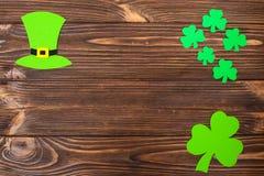 Ζωηρόχρωμο οριζόντιο έμβλημα θέματος ημέρας του ST Πάτρικ ` s Πράσινα φύλλα καπέλων και τριφυλλιών leprechaun στο καφετί ξύλινο υ Στοκ εικόνα με δικαίωμα ελεύθερης χρήσης
