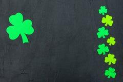 Ζωηρόχρωμο οριζόντιο έμβλημα θέματος ημέρας του ST Πάτρικ ` s Πράσινα φύλλα τριφυλλιών στο μαύρο υπόβαθρο Αισθητά στοιχεία τεχνών Στοκ φωτογραφία με δικαίωμα ελεύθερης χρήσης