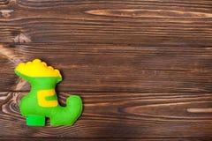 Ζωηρόχρωμο οριζόντιο έμβλημα θέματος ημέρας του ST Πάτρικ ` s Πράσινο χέρι leprechaun - γίνοντα παπούτσι με το χρυσό στο καφετί ξ Στοκ φωτογραφία με δικαίωμα ελεύθερης χρήσης