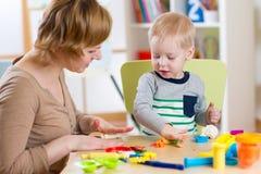 Ζωηρόχρωμο παιχνίδι αργίλου παιχνιδιού αγοριών και μητέρων παιδιών στο βρεφικό σταθμό Στοκ φωτογραφίες με δικαίωμα ελεύθερης χρήσης