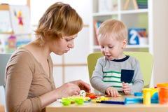 Ζωηρόχρωμο παιχνίδι αργίλου παιχνιδιού παιδιών και γυναικών στο βρεφικό σταθμό Στοκ Φωτογραφία